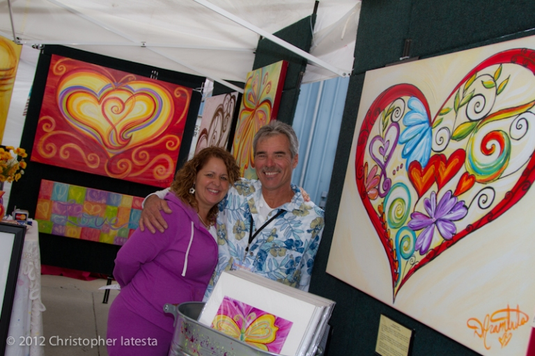 Debbie and Steve Arambula in her colorful art booth in Monterey California